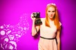 Leinwandbild Motiv young blondie with a camera and pink background