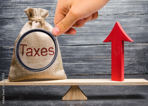 Fotografía  Magnifying glass is looking at a bag with the inscription taxes and a red arrow up on the scales