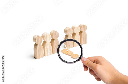 Photo Magnifying glass is looking at a fake person falls out of the line of human figures