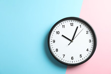 Big Beautiful Office Clock On Two Tone Solid Color Pink And Light Blue Background