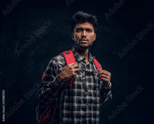 Portrait of a handsome Indian student with a backpack wearing a plaid shirt Canvas Print