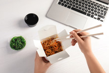 Woman Eating Tasty Chinese Noodles At Workplace, Closeup. Food Delivery