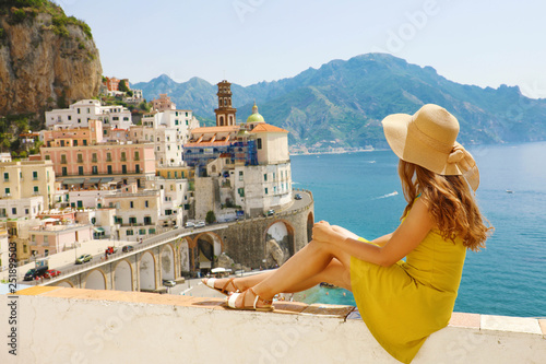 Montage in der Fensternische Honig Beautiful young woman with hat sitting on wall looking at stunning panoramic village of Atrani on Amalfi Coast, Italy