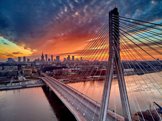 Fototapeta Mosty Beautiful panoramic aerial drone sunset view to Warsaw city center with skyscrapers and Swietokrzyski Bridge (En: Holy Cross Bridge) - is a cable-stayed bridge over the Vistula river in Warsaw, Poland