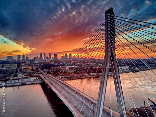 Fototapeta Beautiful panoramic aerial drone sunset view to Warsaw city center with skyscrapers and Swietokrzyski Bridge (En: Holy Cross Bridge) - is a cable-stayed bridge over the Vistula river in Warsaw, Poland obraz