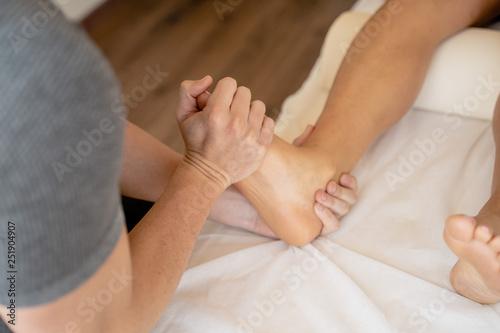 Manos de fisioterapeuta tratando lesión de pie de una mujer Wallpaper Mural
