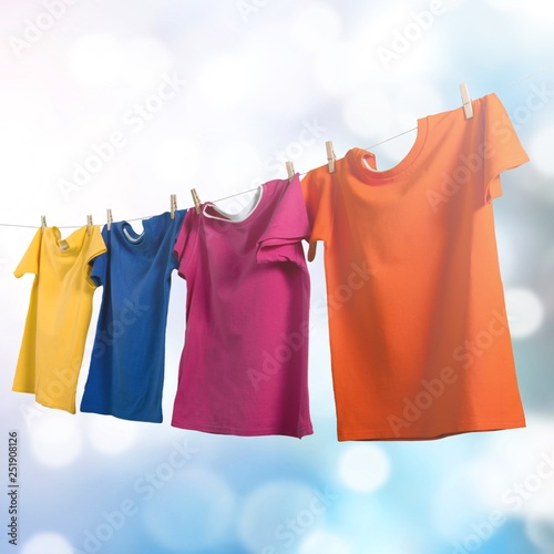 Fotografía  Wash clothes on a rope with clothespins on background