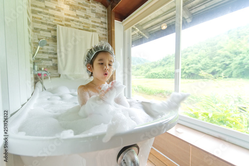 Canvas Print Asian Child girl taking bath in a bath tub washing hair with shampoo and soap