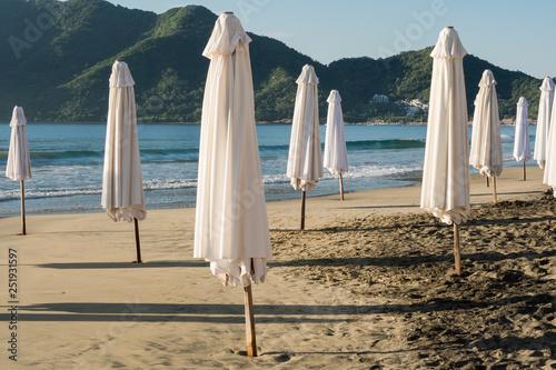 Fotografie, Obraz  Las sombrillas blancas están cerradas en la orilla de la playa.