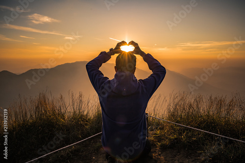 Poster Brun profond Man acting heart hand shape in San Knok Wua hill at Khao Laem National Park Thailand with sunrise background.