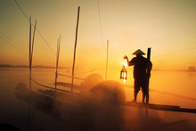 Asian Fishermen Hold Fishing Equipment On Their Boats To Wait For Fish In The Mekong River. In The Morning Of The New Day