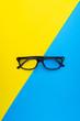 Leinwandbild Motiv Black frame eyeglasses on blue and yellow background
