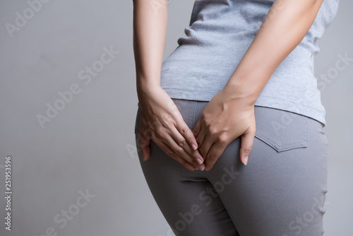 Photo Woman suffering from hemorrhoids and hand holding her bottom because having Abdominal pain