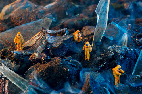 Valokuva  Conceptual photo of toy people in hazmat suits and wings of a dead dragonfly