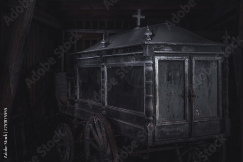 Fotografie, Obraz  Old and dusty funeral horse carriage or hearse abandoned in a barn