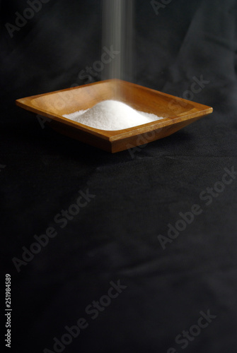 縦長で黒い布背景の上にある正方形の木の器に白い塩が盛られて