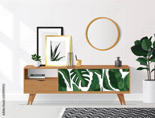 Wooden sideboard with plants and posters on it against white wall Fototapet
