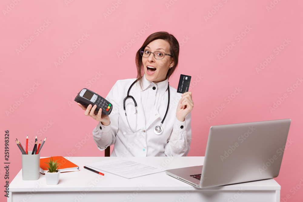 Fototapeta Female doctor sit at desk work on computer with medical document credit card in hospital isolated on pastel pink wall background. Woman in medical gown glasses stethoscope. Healthcare medicine concept
