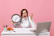 Female Doctor Sit At Desk Work On Computer With Medical Document Hold Clock In Hospital Isolated On Pastel Pink Wall Background. Woman In Medical Gown Glasses Stethoscope. Healthcare Medicine Concept.