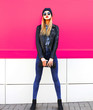 canvas print picture - Stylish blonde woman in full-length wearing rock black style jacket, hat, with handbag clutch on city street over colorful pink wall background