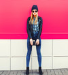 canvas print picture - Stylish blonde woman model in full-length posing wearing rock black style jacket, hat, with handbag clutch on city street over colorful pink wall background