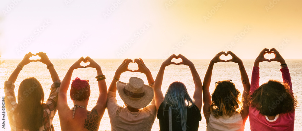 Fototapeta Group of diversity alternative young woman enjoying the sunset at the sea doing hearth symbol with hands - people enjoying friendly lifestyle - vacation in friendship concept for females