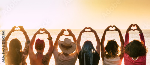 Obraz Group of diversity alternative young woman enjoying the sunset at the sea doing hearth symbol with hands - people enjoying friendly lifestyle - vacation in friendship concept for females - fototapety do salonu