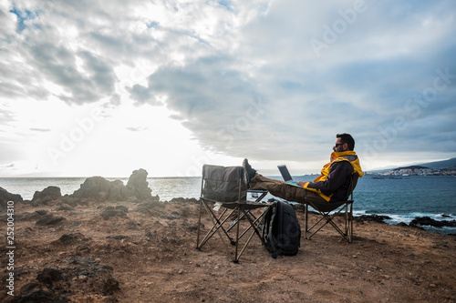 Obraz Digital nomad and traveler middle age adult man sitting and working with internet and laptop in totally fredom in front of the ocean - backpacker lifestyle and alternative office for happy life - fototapety do salonu