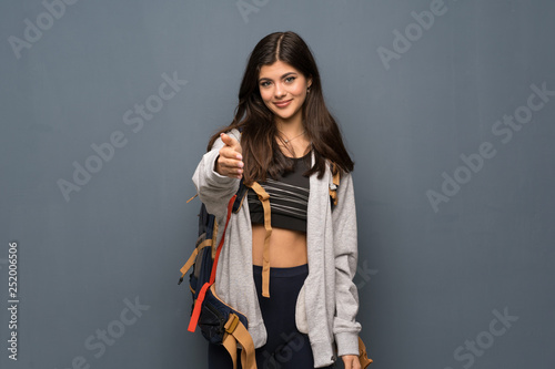 Teenager traveler girl over wall shaking hands for closing a good