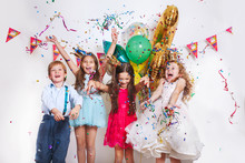 Group Of Beautiful Kids Throwing Colorful Confetti And Looking Happy On Birthday Party