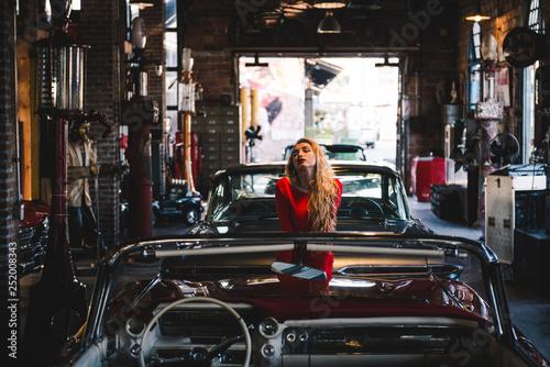 Fotografie, Obraz  Sexy blond woman in red dress near retro car in old garage