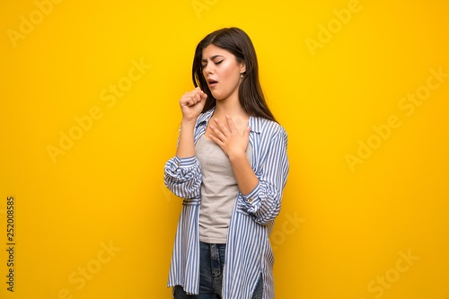 Carta da parati  Teenager girl over yellow wall is suffering with cough and feeling bad