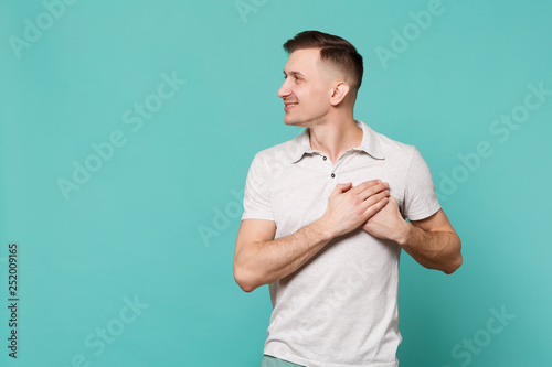 Portrait of smiling young man in casual clothes looking aside, holding hands on heart, chest isolated on blue turquoise wall background Canvas Print