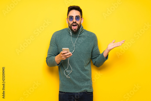 Poster de jardin Magasin de musique Handsome man with sunglasses surprised and sending a message