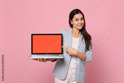 Fotografía  Smiling woman in striped jacket pointing index finger on laptop pc computer with blank empty screen isolated on pink pastel background