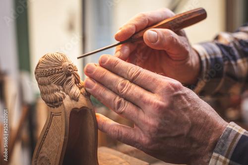Fotografía Hände eines Mannes beim Schnitzen einer Holzfigur