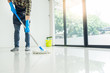 canvas print picture - Young housekeeper cleaning floor mobbing holding mop and plastic bucket with brushes, gloves and detergents in the leaving room house floor helping his wife.