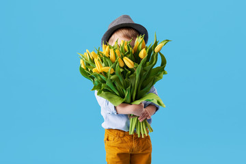 FototapetaCute smiling child holding a beautiful bouquet of yellow tulips in front of his face isolated on blue. Little toddler boy gives a bouquet to mom