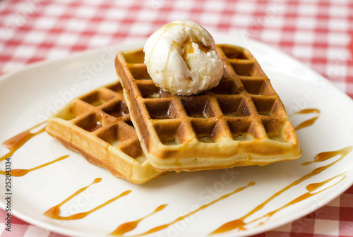 Fotografía  Plate of belgian waffles with ice cream and caramel sauce on red checkered table