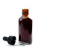 canvas print picture - Homeopathic remedy and liquid tincture medicines concept with close up on a brown medicine glass bottles with the dropper out isolated on white background with copy space