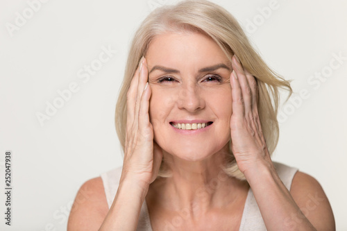 Happy mature woman touching face isolated, anti aging beauty concept Canvas Print