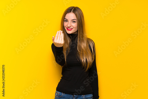 Photo  Young pretty woman over yellow background inviting to come with hand