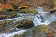 Small Forest Waterfall In Autumn. Beautiful Nature Scenery On The River. Clear Water, Fallen Foliage And Moss On The Boulders. View From Above