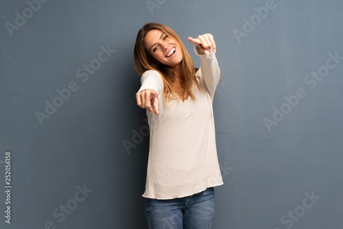 Fotografie, Obraz  Blonde woman over grey background points finger at you while smiling
