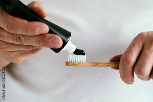 Man with a black toothpaste and a bamboo toothbrush Canvas Print