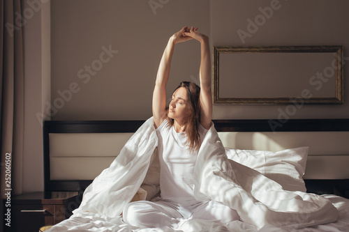 Obraz Young girl is stretching herself awake in her bed and looking through the window. Concept of good morning and good mood for doing new things - fototapety do salonu