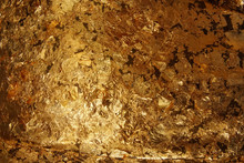 The Dark Gold Leaf Foil Texture Background.