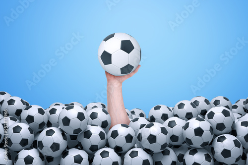 Foto Man's hand emerging from below a lot of footballs and holding one football up