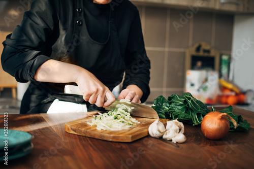 Fotografie, Obraz  Female chef chopping raw vegetables on a wooden board