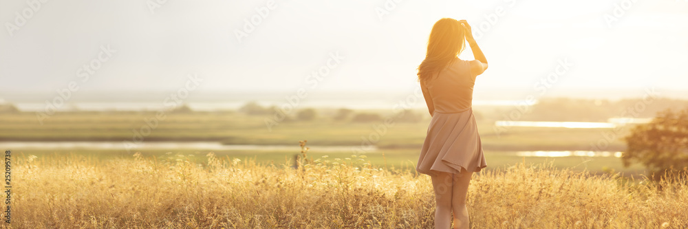 Fototapety, obrazy: dreamy girl in a field at sunset, a young woman in a haze from the sun enjoying nature, romantic style